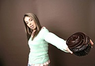 View of a teenage girl holding a chocolate cake