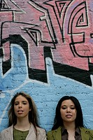 Portrait of two women near a wall