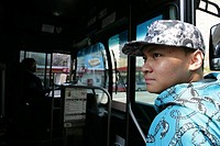 Teenage boy 15-17 standing by bus, side view