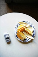 Slices of orange and mobile phone on table