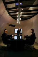 Three people inside a conference room