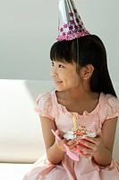 Birthday girl with cupcake looking sideways