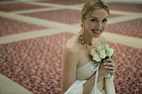 Mature woman holding a bouquet smiling (thumbnail)