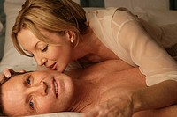 Mature couple in bed kissing (thumbnail)