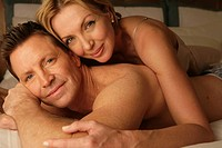 Mature couple in bed smiling