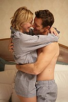 Mature couple in bed hugging each other