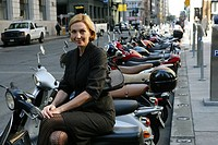 Business woman sitting on a scooter