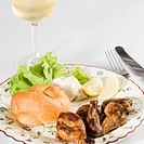 Close-up of roasted chicken and bun in a plate with a glass of wine