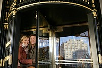 Mature couple in between revolving doors (thumbnail)
