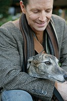 Mature man with a Whippet (thumbnail)