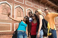 Young woman standing with her friends and taking a picture of themselves, Taj Mahal, Agra, Uttar Pradesh, India