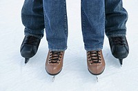 Two people wearing jeans on ice skates