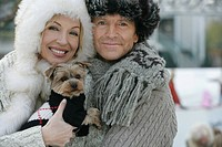 Mature couple holding a Yorkshire Terrier
