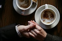 Aerial view of a couple holding hands next to two coffee mugs