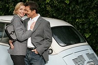 Mature couple leaning on a car