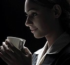 Close-up of a businesswoman holding a coffee cup and looking away