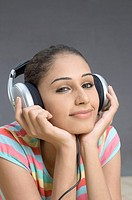 Portrait of a young woman listening to music and smirking