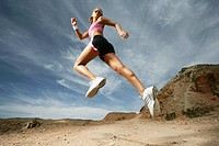 Caucasian woman jumping up in air during exercise