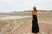 Caucasian woman in the desert with her arms outstretched