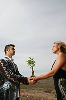 Couple holding a sapling in their hands together