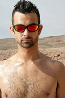 Caucasian man shirtless wearing shades outdoors