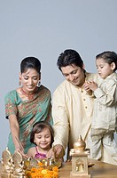 Couple decorating a pooja thali with their children