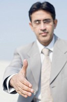 Close-up of a businessman extending his hand for handshake