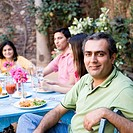 Portrait of a mid adult man with his friends sitting at a dining table