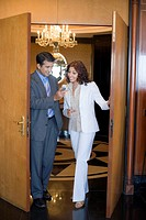 Businessman and a businesswoman looking at a mobile phone and smiling in a hotel
