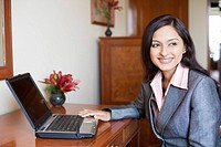 Close-up of a businesswoman using a laptop and smiling