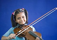 Portrait of a schoolgirl playing a violin and smiling