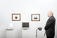 A man in a museum looking at office equipment