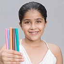 Portrait of a girl holding pens and smiling