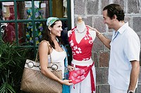 Mid adult couple standing near a mannequin and smiling