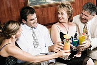 Mid adult couple with a mature woman and a senior man toasting glasses of cocktail
