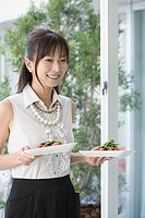Young woman with plates of salad