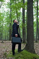 Portrait of young businessman in forest with cellular phone