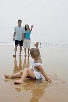 Boy waving goodbye to parents on beach