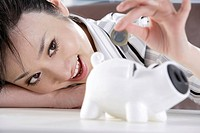 Young woman inserting coin in piggy bank