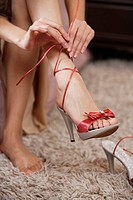 Woman putting on sandal, low section