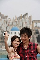 Young couple taking self portrait with digital camera at amusement park, smiling