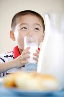 Boy drinking milk behind bread