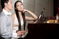 Young woman looking at man playing grand piano