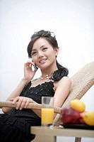 Young woman relaxing in reclining chair and using mobile phone