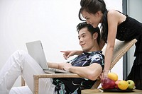 Girl pointing towards laptop and man sitting on wicker chair