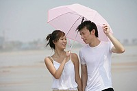 Young couple at beach with umbrella