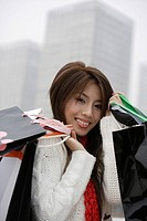 Portrait of a young woman smiling and holding shopping bags