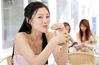 Young woman drinking beverage with straw