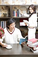 Young man reading book while woman smiling in background