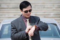 Mid adult man with sunglasses looking at wristwatch